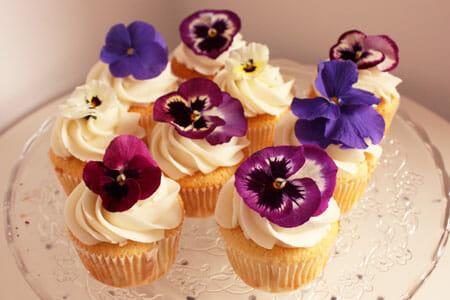 Покройте остывшие кексы глазурью и украсьте засахаренными цветами